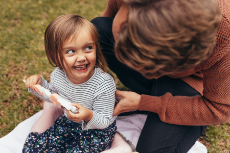 Smiling girl sitting with her father outdoors holding a sugar candy stick. Father and daughter spending time together eating sugar candy.