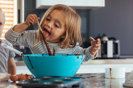 Little girl licking spoon while mixing batter for baking in kitchen  and her brother standing by. Cute little children making batter for baking. 스톡 콘텐츠