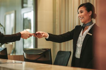 Recepcionista sonriente detrás del mostrador del hotel asistiendo a invitada. Conserje entregando los documentos al huésped del hotel. Foto de archivo