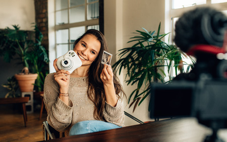 Woman showing a photograph taken using an instant camera while video recording content for her blog sitting at home. Blogger recording content for her blog on a camera mounted on tripod.