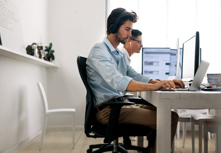 Software developers sitting at office working on computers wearing headphones. Application developer working on a laptop in office.