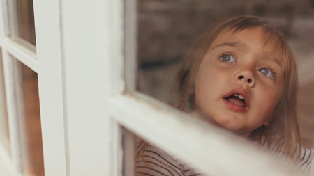 Close up of a little girl sitting beside a window and looking outside. Grey eyed girl looking outside sitting at the window.