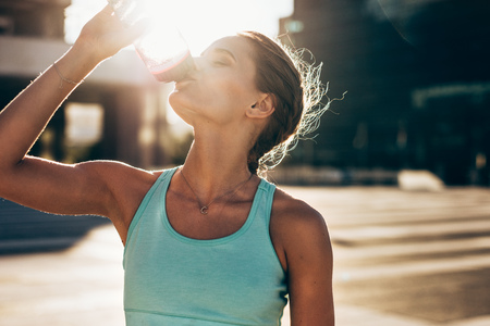 Fit young woman drinking water after workout session. Thirsty female athlete drinking water outdoors. Imagens - 102367954