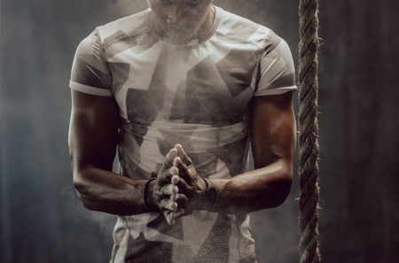 Athletic man chalking his hands before climbing a rope at the gym. Man standing beside a hanging rope applying gripping powder to his hands. 版權商用圖片