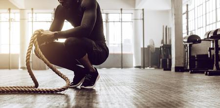Uomo seduto sulle punte dei piedi che tiene un paio di funi di battaglia per l'allenamento. Ragazzo di Crossfit in palestra, allenandovi con la corda fitness.