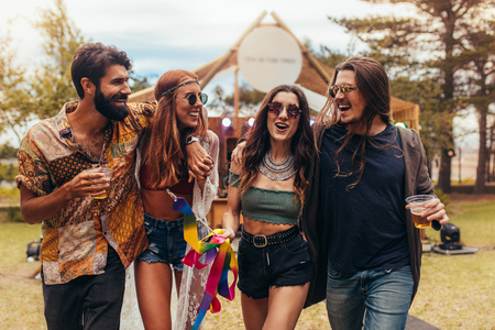 Group of men and women at music festival having beers and enjoying. Friends having a great time at music festival in a park. Stock Photo