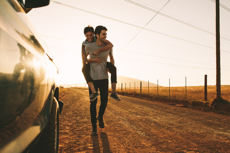 Woman piggy riding on a man outdoors in country side. Man carrying a woman on his back while on a road trip. Stok Fotoğraf