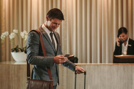 Gelukkige zakenman die zich in hotellobby bevindt en mobiele telefoon met behulp van. Zakenreiziger aankomen bij zijn hotel met telefoon en koffer. Stockfoto