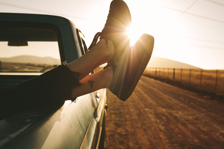 Close up of legs of a woman relaxing at the back of a pick up truck on a highway in country side. Legs hanging out from car with sun in the background.