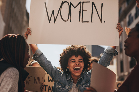 Laughing young woman holding a banner during a protest. Group of females activist protesting on road for women empowerment. Reklamní fotografie