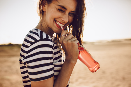 Portrait of cheerful young woman drinking beverage with straw from glass bottle. Girl drinking a soda outdoors on a summer day.