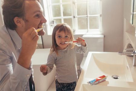 Father and daughter brushing teeth standing in bathroom. Man teaching his daughter how to brush teeth. Stock Photo - 102933058