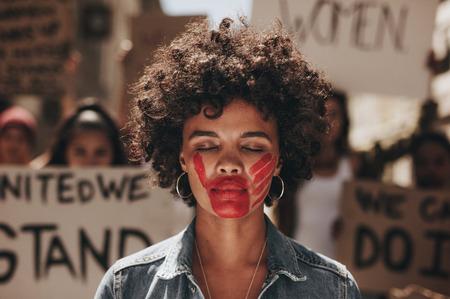 Mujer de pie al aire libre con la huella de una mano ensangrentada en la boca durante la manifestación. Protestando para detener el abuso de las mujeres.