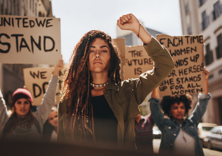 Woman leading a group of demonstrators on road. Group of female protesting for equality and women empowerment. Archivio Fotografico