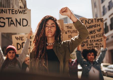 Femme à la tête d'un groupe de manifestants sur la route. Groupe de femmes protestant pour l'égalité et l'autonomisation des femmes.