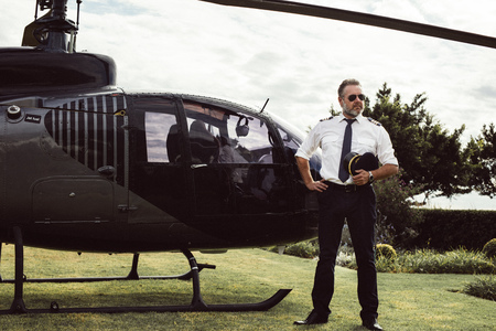 Mature male pilot in uniform standing outside with a private helicopter. Private helicopter parked in the lawn with male pilot waiting.
