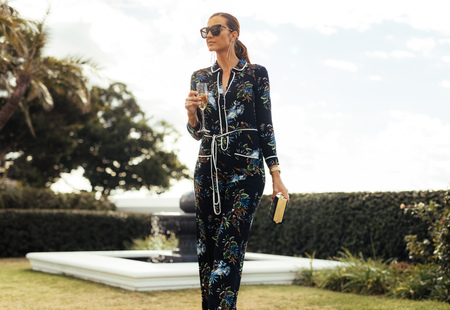 Gorgeous woman walking in lawn with glass of wine. Stylish wealthy female with wine walking outdoors.