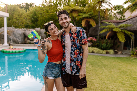 Cheerful young couple standing by the pool with water gun. Woman holding water gun standing with her boyfriend. Both fully wet with water.