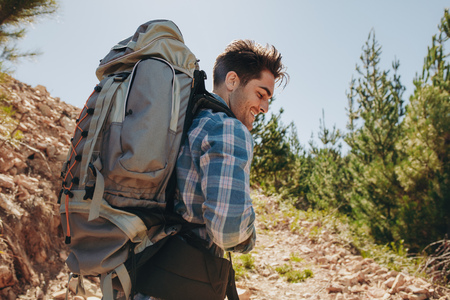 Rear view shot of smiling young guy with backpack hiking on mountains. Caucasian male hiker trekking on mountain. Stock fotó
