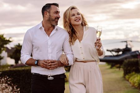 Hombre guapo con su hermosa novia caminando juntos al aire libre. Hermosa pareja caminando al aire libre con un helicóptero en la parte de atrás.