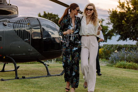 Two young women walking away from a helicopter with a glass of wine in their hands. Best friends walking together with wine and having fun.