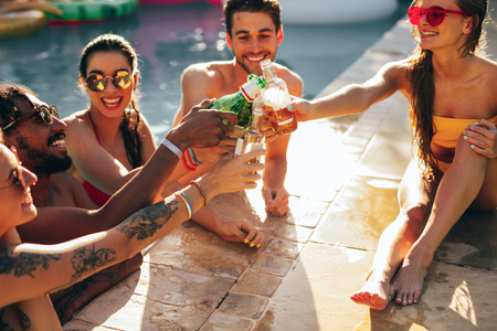 Friends having beers at pool party. Multiracial men and women enjoying and toasting drinks at pool party.