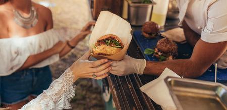 Frauenhand, die nach einem Burger am Imbisswagen greift. Nahaufnahme des Imbisswagenverkäufers, der Burger zum weiblichen Kunden dient.