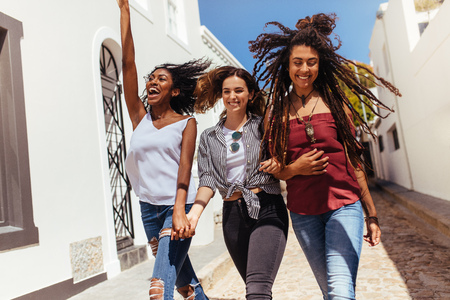 Three happy looking women walking on street wearing fashionable clothes on a sunny day. Young woman jumping in joy while walking with friends on a street.