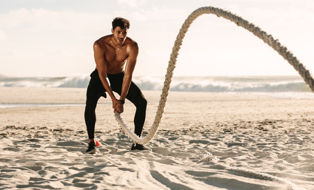 Man doing fitness workout at a beach on a sunny day. Bare chested man doing workout using a battle rope on the beach.