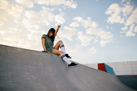 Happy urban woman in skate park having fun. Female skateboarder sitting on a ramp.