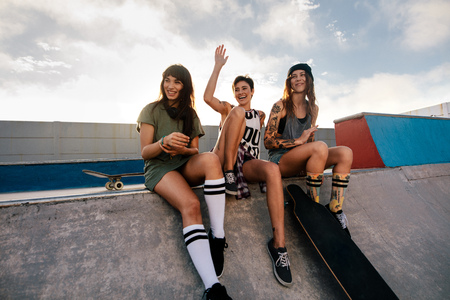 Group of female friends sitting on ramp in skate park and smiling. Three women enjoying a day at skate park. Stock Photo