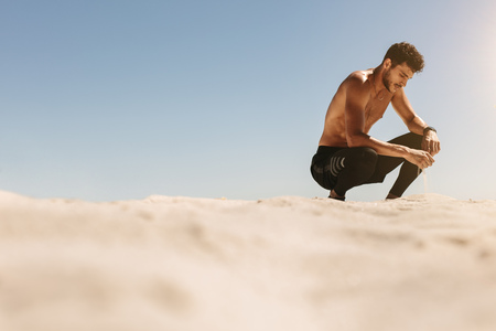 Man sitting on his toes and relaxing during workout at the beach. Bare chested man sitting at the beach in fitness gear and touching sand during workout. 写真素材