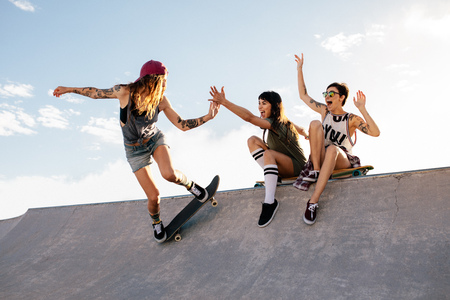 Female skateboarder riding skateboard at skate park with friends sitting on ramp having fun. Woman skater giving high five to female friend sitting on ramp during her routine.