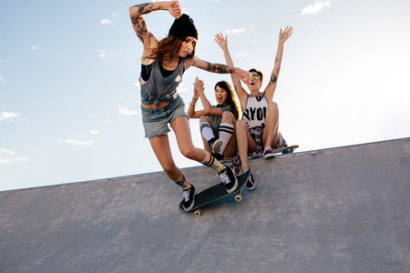 Skater girl rides on skateboard with female friends sitting on ramp cheering. Female skateboarding at skate park with friends cheering.