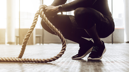Close up of a man sitting on his toes holding a pair of battle ropes for workout. Crossfit guy at the gym working out with fitness rope.