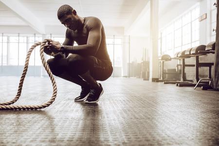 Uomo seduto sulle punte dei piedi che tiene un paio di funi di battaglia per l'allenamento. Ragazzo di Crossfit in palestra, allenandovi con la corda fitness. Archivio Fotografico
