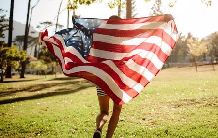 Rear view of young woman running in the forest with American Flag. American girl celebrating fourth of july in the park.