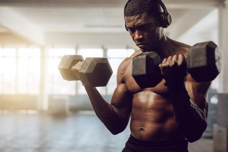 Uomo a torso nudo che ascolta la musica durante l'allenamento in palestra. Uomo atletico sollevamento manubri indossando cuffie wireless.