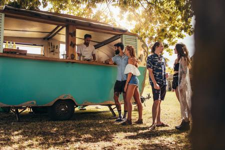 Jongeren kopen straatvoedsel van een foodtruck in het park. Groep mannen en vrouw bij voedselvrachtwagen.