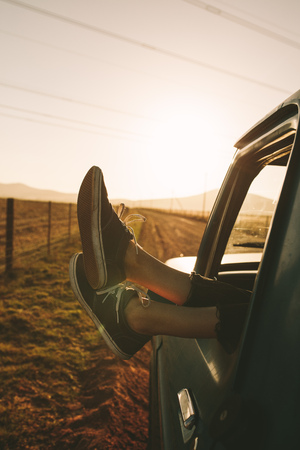 Close up of legs of a relaxing woman hanging out from car on a highway in country side. Legs hanging out from car.