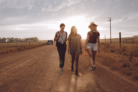 Full length of three disappointed women walking through country road leaving their broken down car behind. Friends leaving broken down car behind on country road. They were going on road trip in countryside. 版權商用圖片