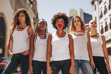 Eine Gruppe von Demonstrantinnen marschiert auf dem Weg zur Stärkung der Frauen. Aktivistinnen in der Kleiderordnung demonstrieren im Freien.