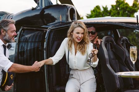 Schöne junge Frau, die einen Hubschrauber mit dem Piloten aussteigt, der sie unterstützt. Wunderschöne junge Frauen, die einen Hubschrauber reisen.
