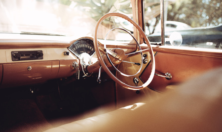 Interior of a classic vintage car. Retro style steering wheel with brown and beige dashboard. Reklamní fotografie