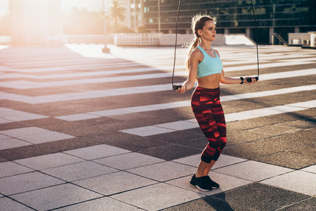 Full length of woman in sportswear skipping ropes outdoors. Female athlete doing cardio workout in morning.
