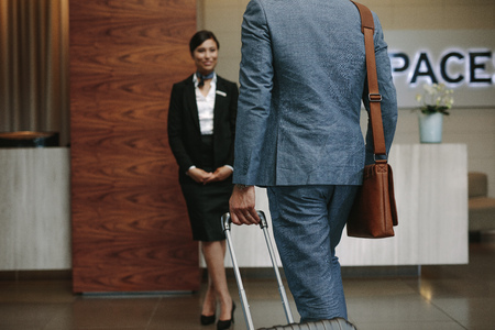 Businessman carrying suitcase and walking towards a receptionist waiting for welcome the guests. Business traveler arriving at hotel for conference.
