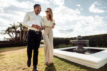 Elegante pareja caminando al aire libre en el césped con una copa de vino. Hombre y mujer mirándose y caminando juntos al aire libre.