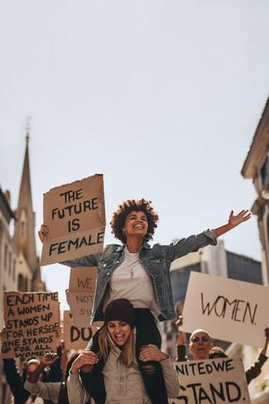 Groep jonge vrouwen die met uithangbord van het protest genieten. Vrouwelijke demonstranten die genieten van het protest onderweg.