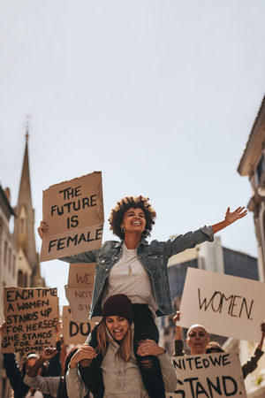Gruppo di giovani womenn con l'insegna che gode della protesta. Dimostranti donne che si godono la protesta su strada.
