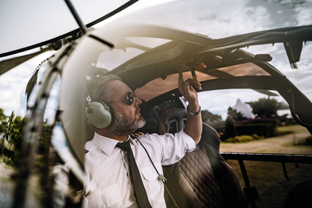 Pilot with headset starting the controls in the private helicopter. Helicopter pilot sitting in the cockpit. Stock Photo
